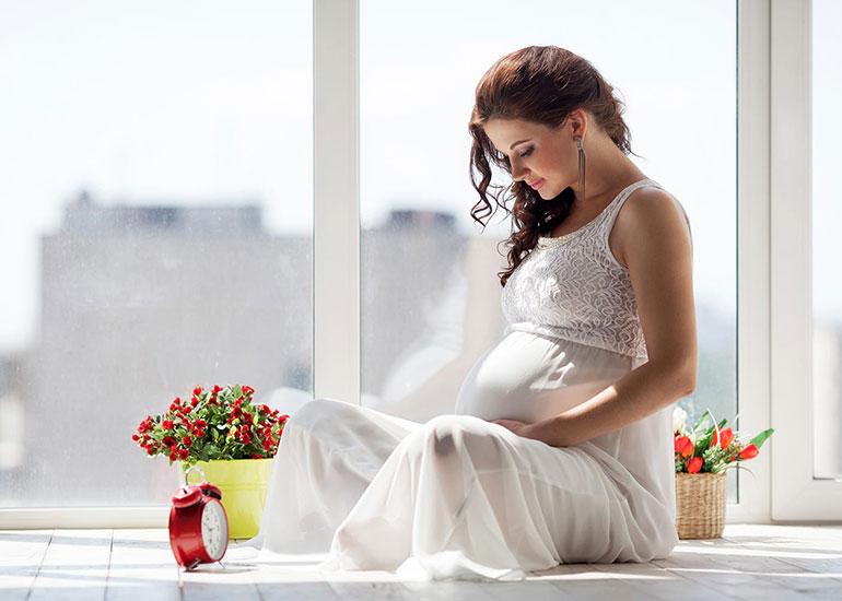 Беременная женщина сидит на окне