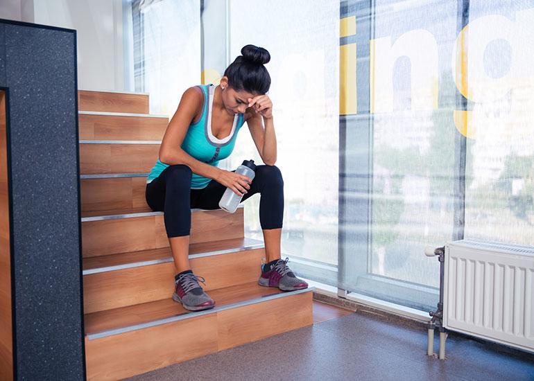 Девушка сидит на лестнице после занятий спортом