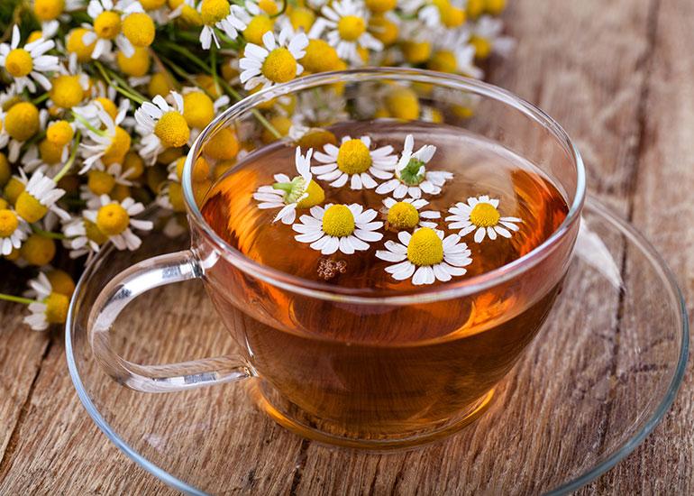 Чашка с настоем и соцветия ромашки