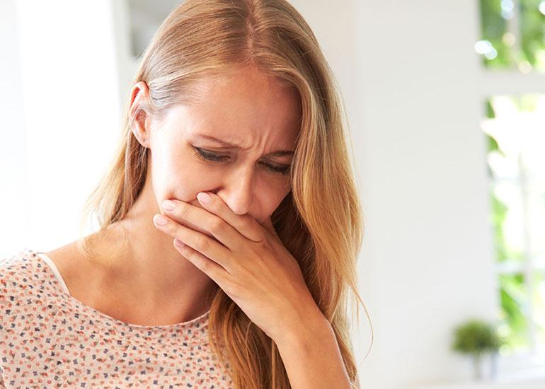 Женщина закрывает при приступе тошноты