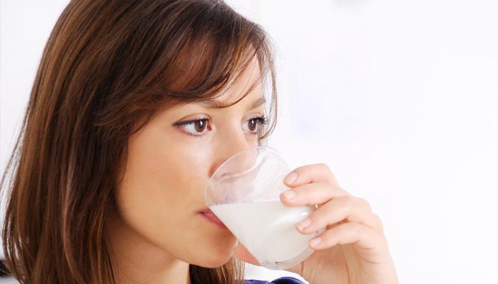 Женщина пьет кефир