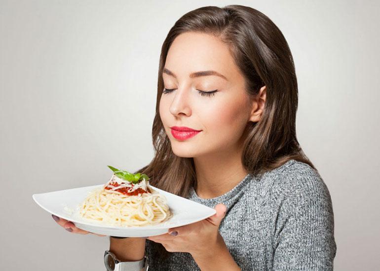 Девушка держит тарелку и вдыхает аромат спагетти
