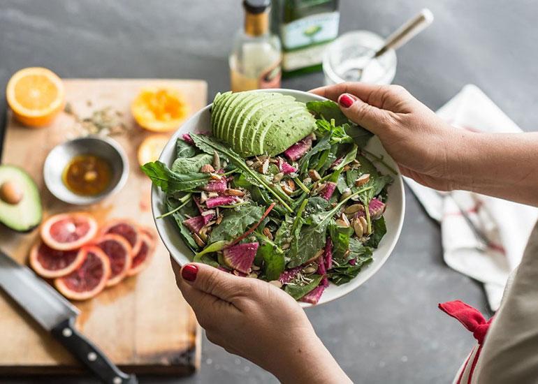 Человек держит тарелку с салатом