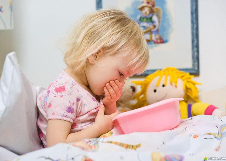 Ребенок держит пластиковый тазик и прикрывает рот