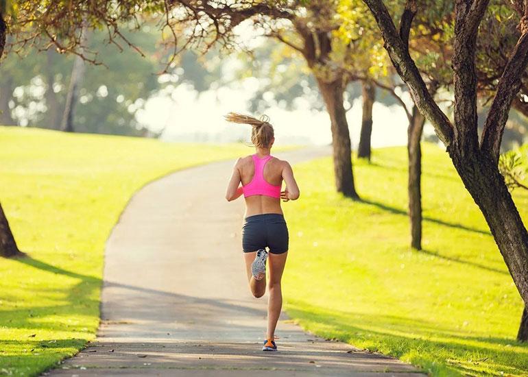 Девушка бегает по парку