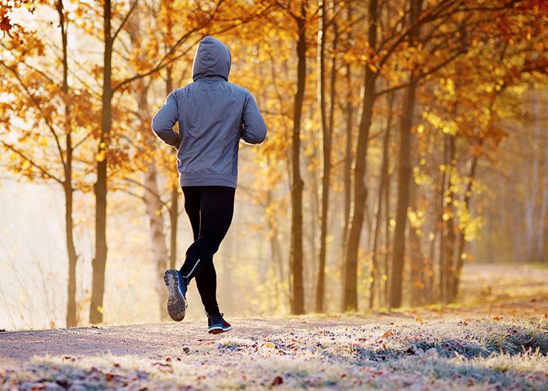 Мужчина бегает по парку осенью